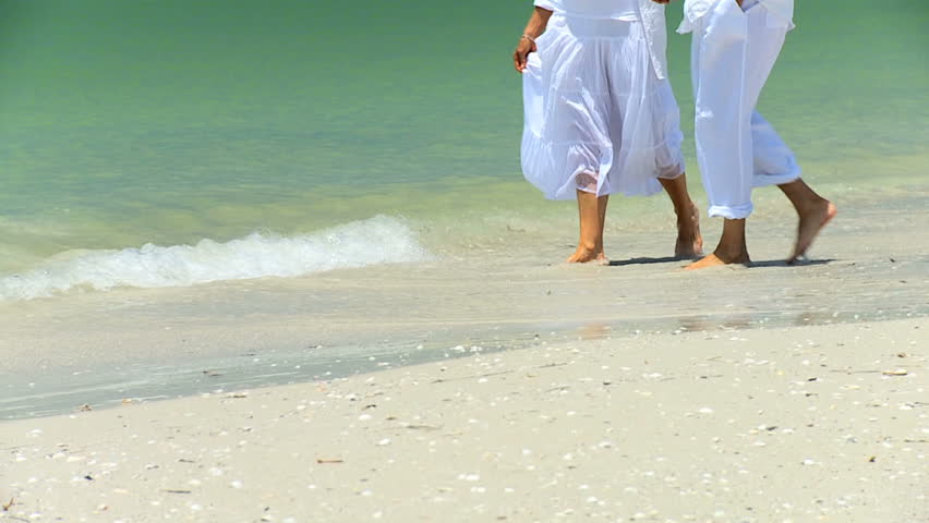 Legs & feet of senior couple having fun splashing barefoot in the shallows on the beach 60FPS
