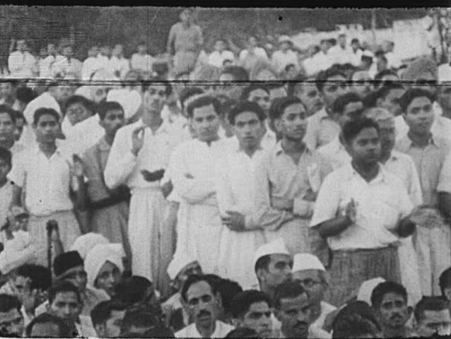 INDIA- CIRCA 1930: Supporters clap and watch from behind barricades as Gandhi walks out of a building.  Gandhi is helped out of a train.