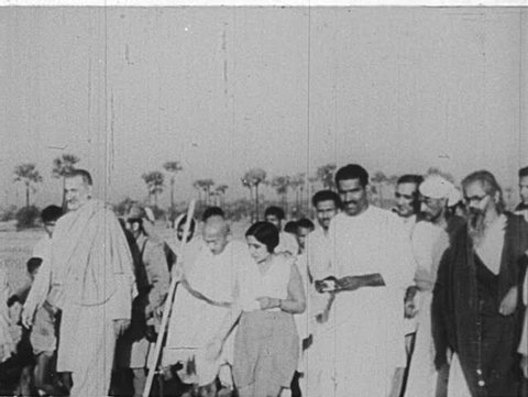 INDIA- CIRCA 1930: A group walks alongside Gandhi.  Gandhi walks a crowd.  He listens to a supporter. He sits. Speaks into a microphone.  He sits on a pillow. Two girls lead him through a crowd.