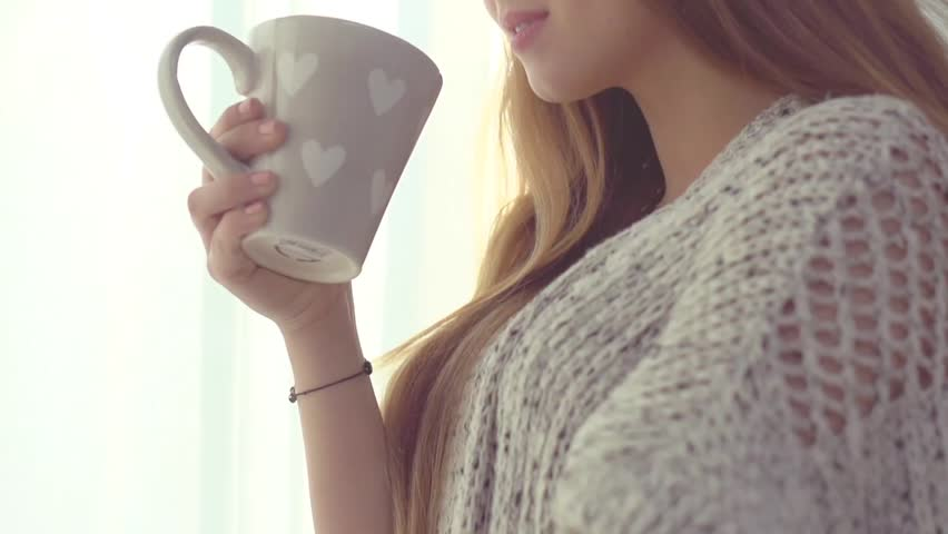Beauty girl looking out the window and enjoying her morning coffee or tea. Beautiful young romantic woman drinking hot beverage at home. Slow motion footage 240 fps. HD 1080p. High speed camera shot