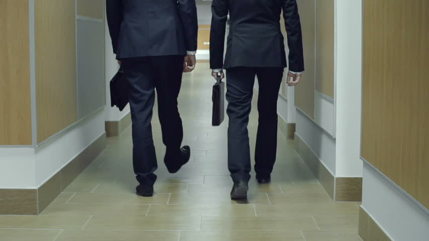 Camera following two anonymous businessmen having discussion in office corridor | Shutterstock HD Video #7909612