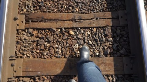 Feet walking down the railway tracks panning up to see the view.	From the point of view of the person, we see legs stepping forward between railroad tracks on a never-ending journey to find paradise.