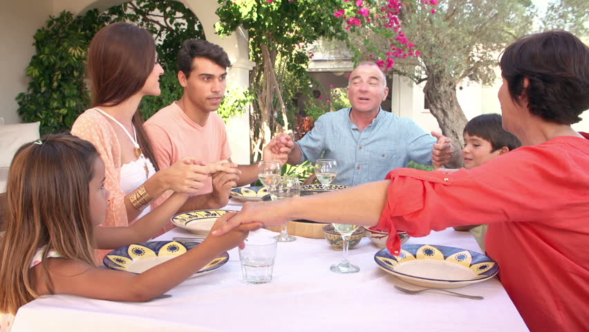 Multi Generation Hispanic Family Join Hands To Pray Before Enjoying Meal On Outdoor Terrace