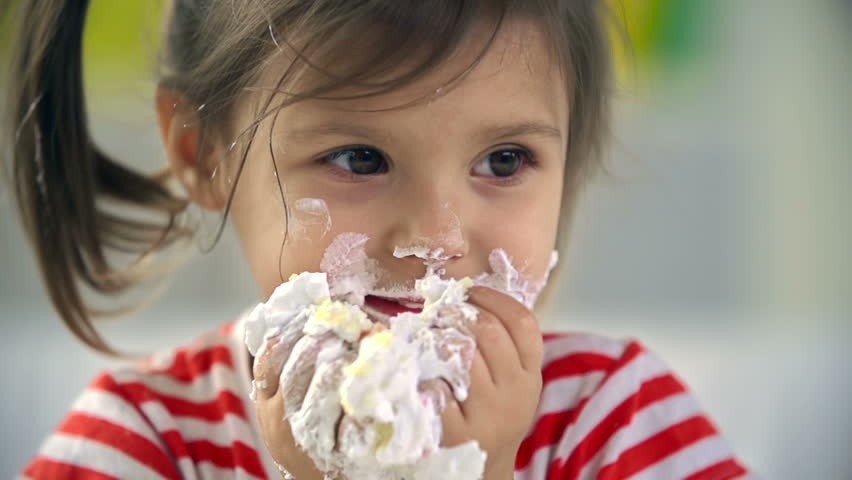 Close up of adorable little girl devouring cake with her hands | Shutterstock HD Video #7920388