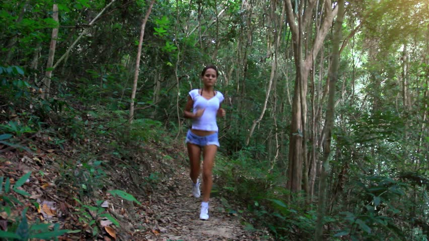 young fitness woman running in jungle forest on koh samui