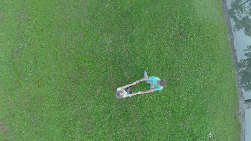 Couple spinning under camera on green grass. Aerial footage of rotating boy and girl holding hands.