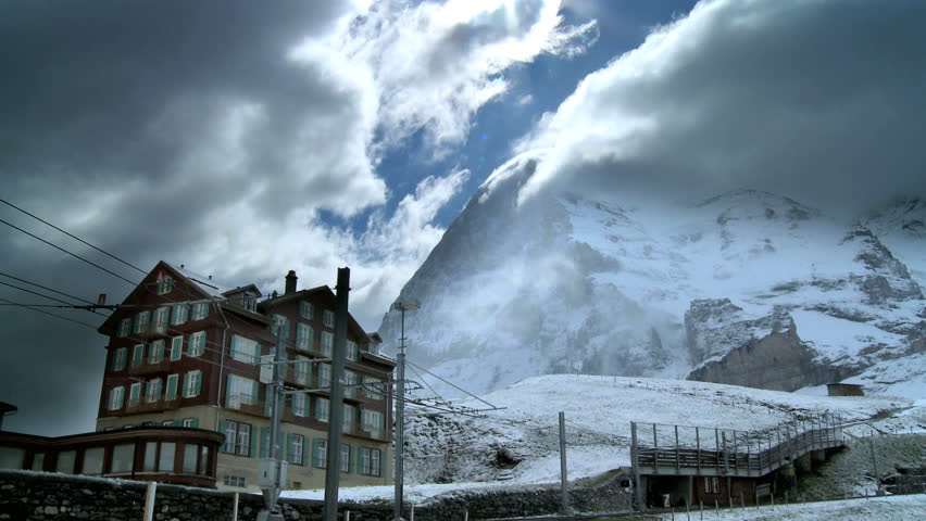Dramatic time-lapse clouds over an alpine hotel with the Eiger mountain, Swiss Alps behind