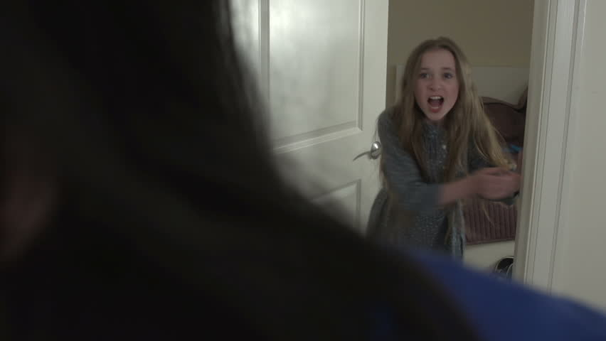 "A mid-shot of a young girl running upset into her bedroom. She clearly mouths ""I hate you"" at her mother - foreground - before slamming the door."