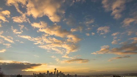 The morning sun lights up a series of alto cumulus clouds over the Seattle skyline.