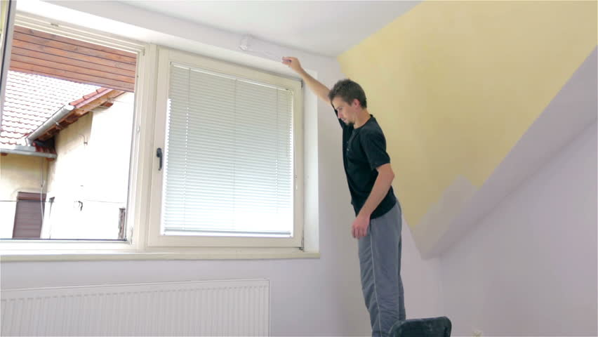 Standing On Chair Painting Around Windows With Roller. Man In Casual  Clothes Doing Paint Job