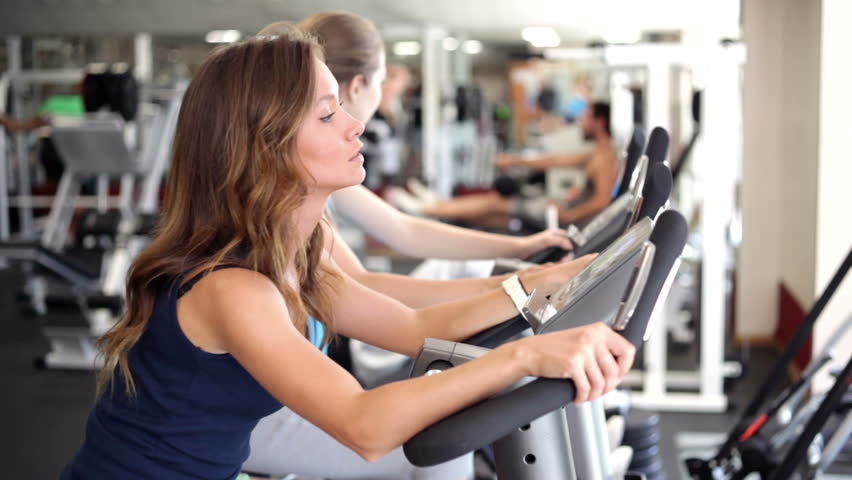 Young women use exercise bicycles in a gym/Using Exercise Bikes