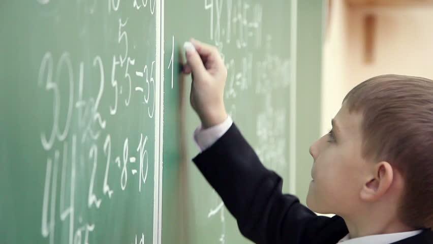 Schoolboy solves math on the school blackboard 3   Shutterstock HD Video #8082232