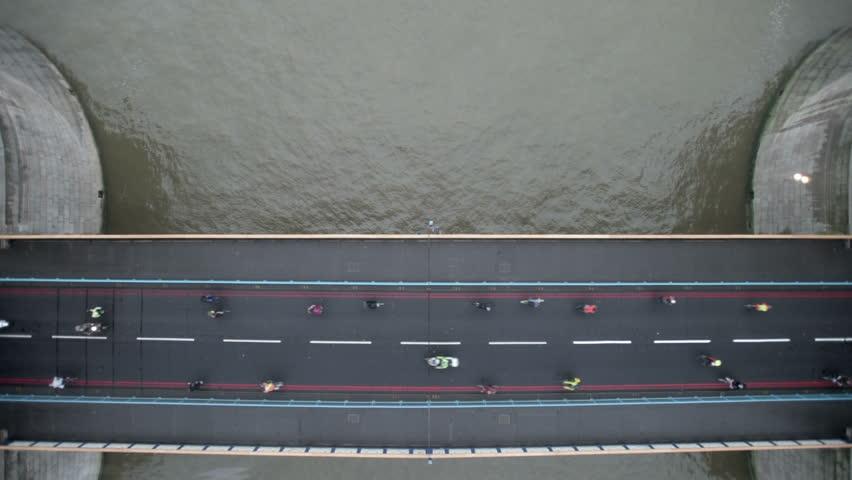 Cyclists flow across Tower Bridge, seen through the new glass floor in the bridge's walkways. The river Thames flows calmly below the bridge.