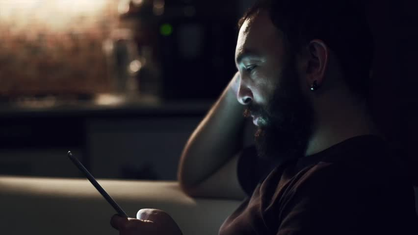 Young man reading his tablet in the dark | Shutterstock HD Video #8171152