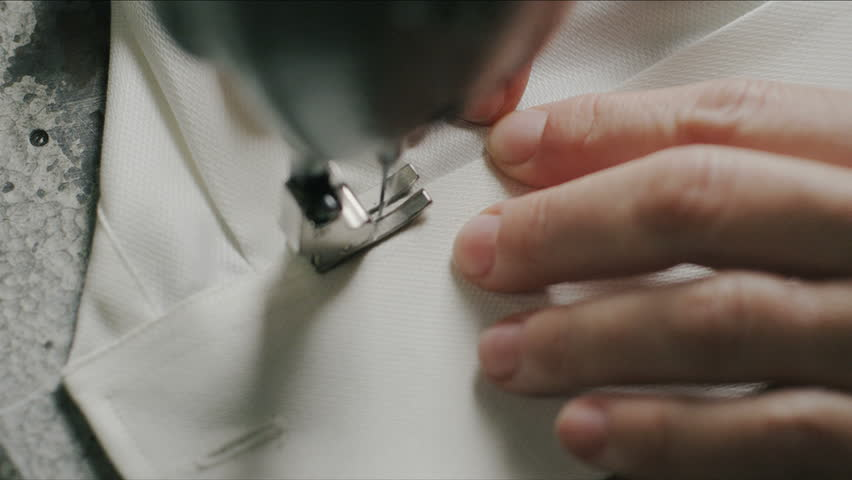 Super slow motion of middle-age woman hand stitching on white fabric with vintage sewing machine (macro close up)