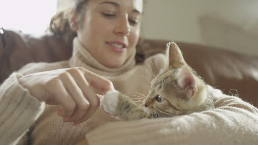 Beautiful woman and kitten at home. Pet cat and young owner relaxing together and enjoying each others company.