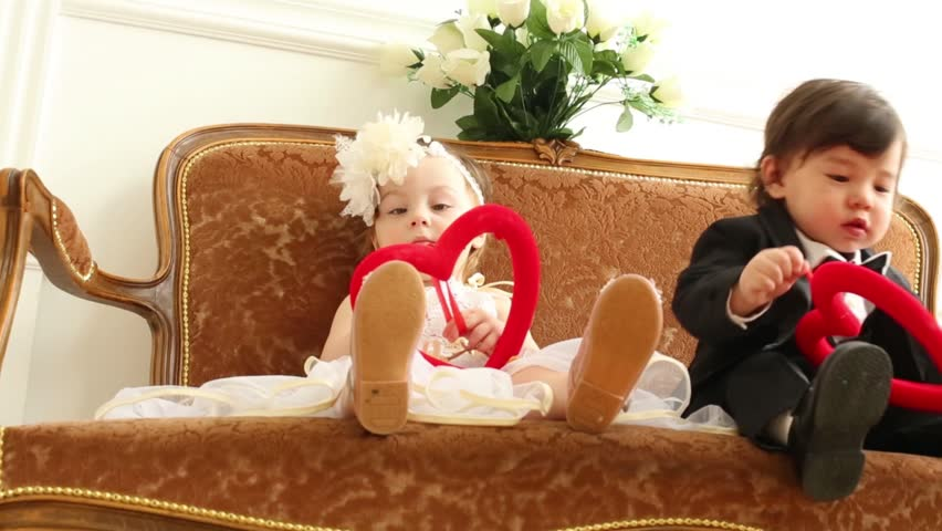 Babies in costumes of bride and groom with red hearts sit on couch. Boy peels off   Shutterstock HD Video #8214022