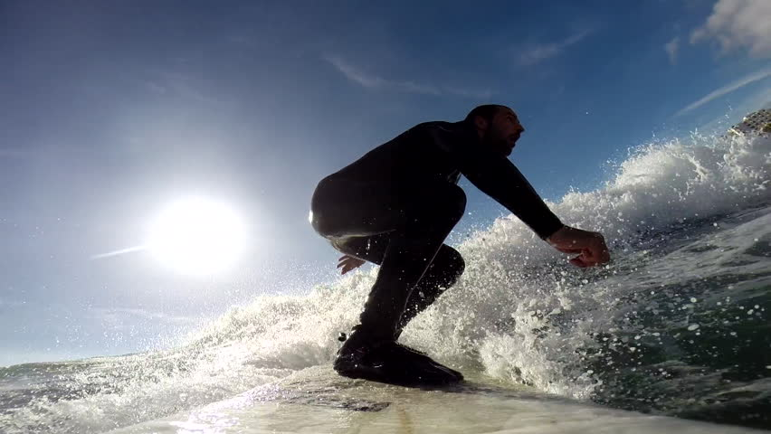 A surfer swiftly riding on the surface of water while maintaining balance, sun visible in the sky, POV   Shutterstock HD Video #8258803