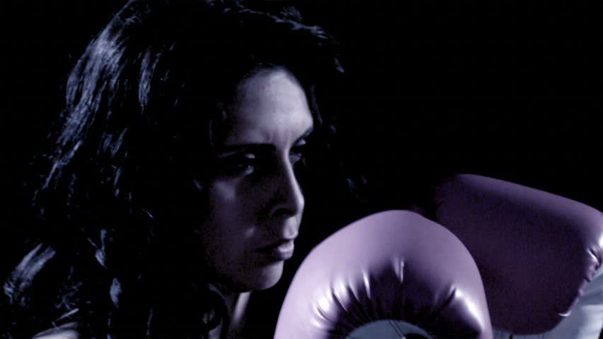 A Latino woman boxes.