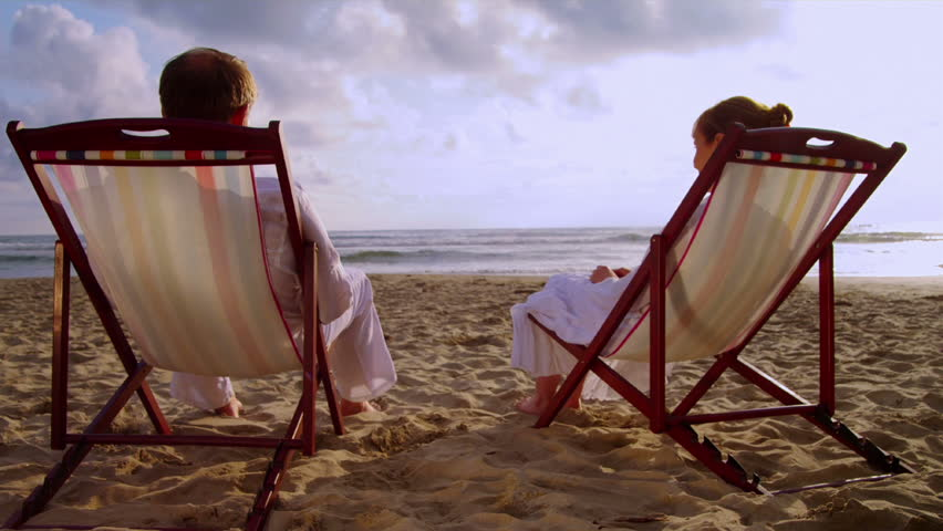 An elderly couple sits on the beach together and holds hands.