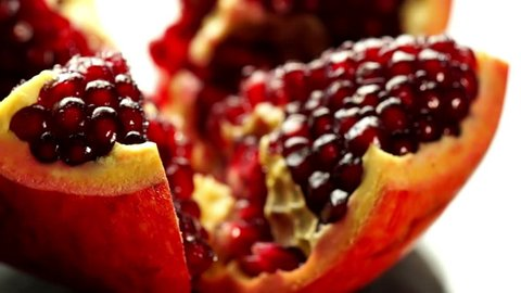 open pomegranate rotates on a light background