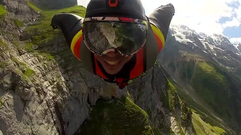A base jumper in a wingsuit gliding down in the air in a mountain landscape, POV