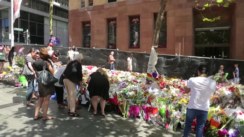 SYDNEY, Australia - DECEMBER 21, 2014: Mourners lay flowers outside the Lindt Cafe where the Sydney Siege took place, during which two hostages lost their lives.