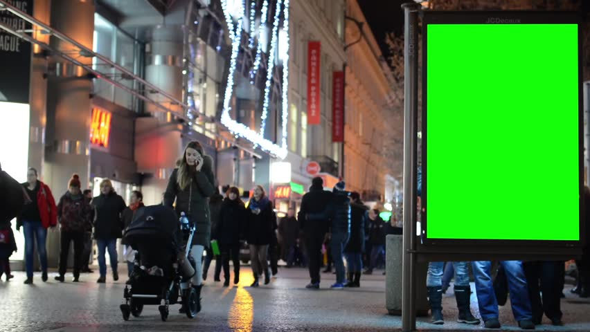 PRAGUE, CZECH REPUBLIC - DECEMBER 2014: billboard in the city - urban street with buildings - green screen - walking people - night