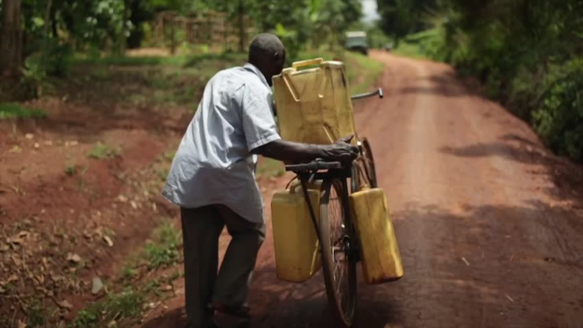MASINDI, UGANDA - SEPTEMBER 2013: African man using a bicycle to collect water in 3 containers pushing bike