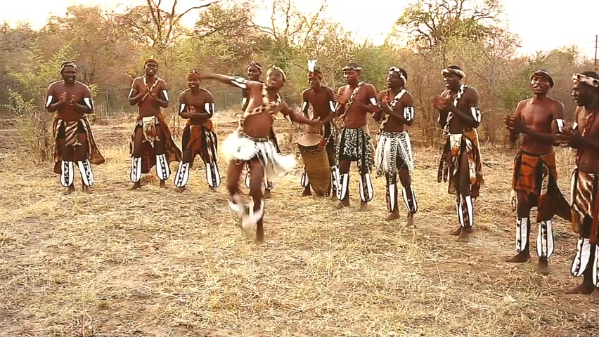 Traditionally dressed African tribesmen of the Herero Tribe dance and sing songs of welcome in Victoria Falls, Zimbabwe, Africa. Drumming, jumping, clapping & singing abound amongst this happy group. | Shutterstock HD Video #8379172