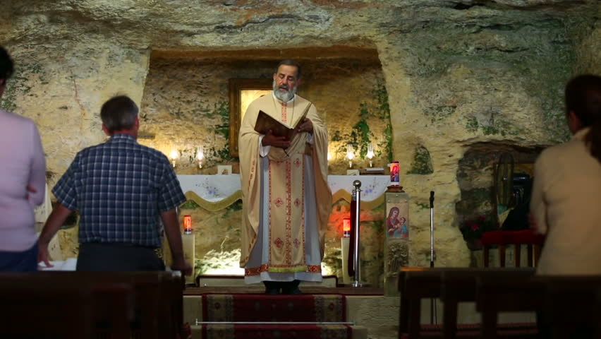 SAIDON, LEBANON - 2014: Priest recites prayers in front of his parishioners in Our Lady of Mantara which is a holy Christian site and a Marian shrine where the Virgin Mary waited for Jesus, dolly shot | Shutterstock HD Video #8388292