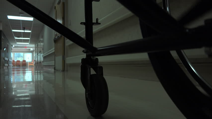 Patient in wheelchair, low angle POV, spins through hallway, heads to dining room, recreation area at assisted living nursing home. 4K UHD 3840x2160