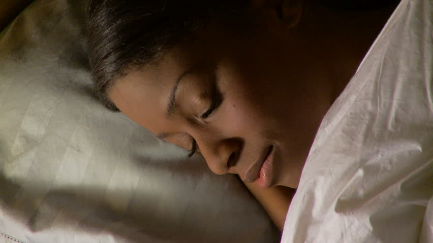 Portrait of young woman sleeping in bed