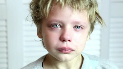 Head and shoulder portrait of caucasian blond boy crying and looking at camera and then closing his face with hands. Parenting, violence in family, bullying, feelings and emotions of children concept.