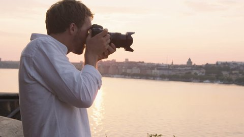 Tourist taking photograph of sunset in Stockholm skyline and Gamla Stan. Man photographer taking photos using SLR camera. Male traveler sightseeing visiting landmarks in Sweden, Scandinavia.