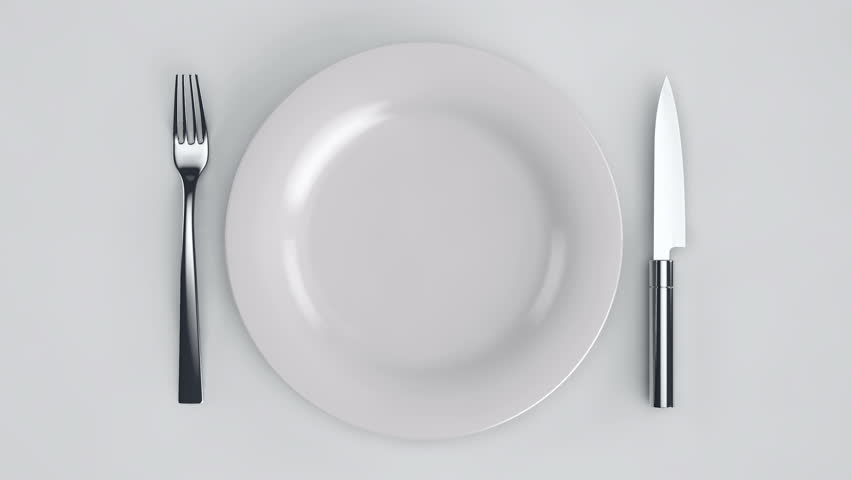 Empty plate. Move a white plate with a knife and fork on a white background.