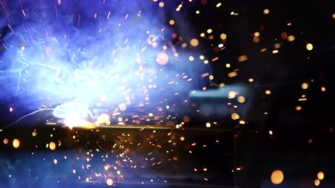 Flashes and lot of sparks from welding work at construction site in dark in slow motion