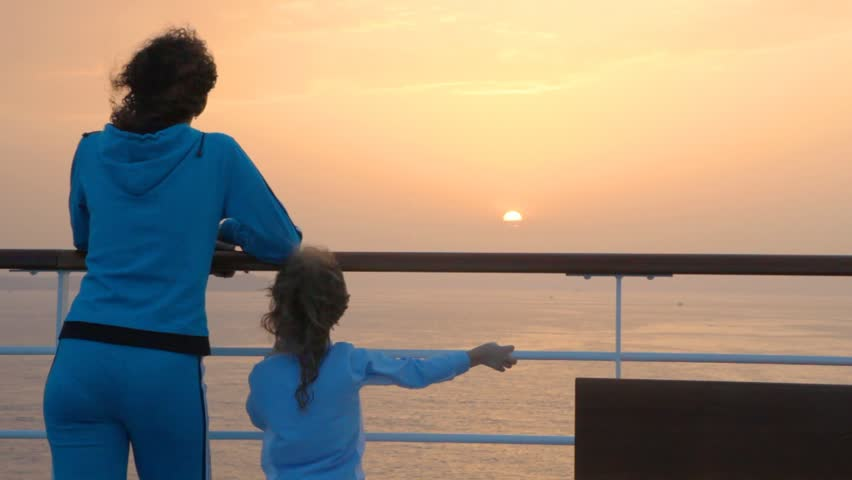 a mother and her little daughter watch the sun set from a ship