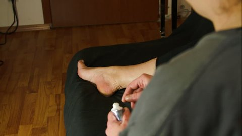 Woman Massaging Her Foot With A Numbing Cream, Over The Shoulder Shot, Rheumatis