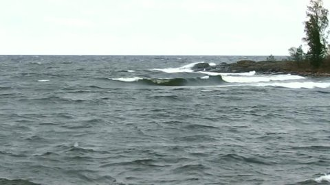Gale-Force Winds over Lake Superior, panoramic bay view with freshwater waves rolling in towards rocky shoreline.