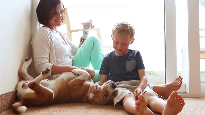 Happy mother and son family on the home floor with friendly beagle dog