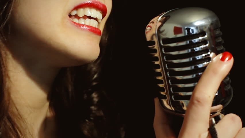A classy young woman singing on stage with a retro vintage microphone (called Elvis or Fatty). Making cool dance moves. Extreme close-up shot, detail of mouth, lips and lipstick, black background.