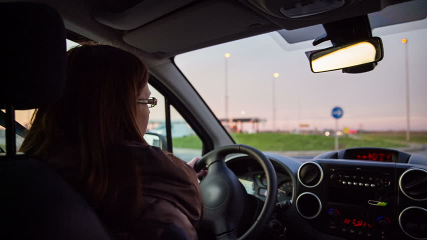 Woman driving car at dawn. Backseat view of female driver driving on road while sun going down. | Shutterstock HD Video #8624002