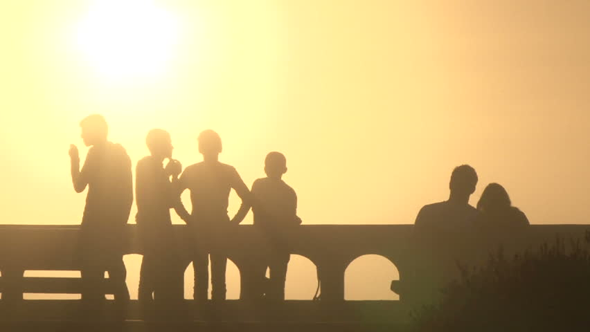 Silhouetted group of boys hanging out on promenade with cute, loving couple on sunny day in Seaside, Oregon.