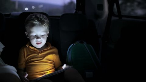 Little boy traveling on backseat of a car at night and using touch pad to entertain himself during the trip