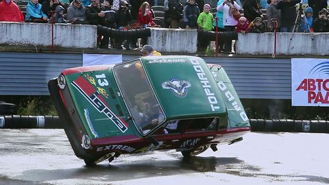 KIEV, UKRAINE - SEPTEMBER 29, 2013 - Bigfoot Crash Show. Stunt performer climbs out of car, driving on two wheels