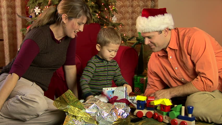 Mother, father and son in pajamas opening Christmas presents