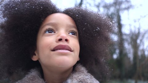 Little girl in wonder at the snowflakes falling around her outdoors