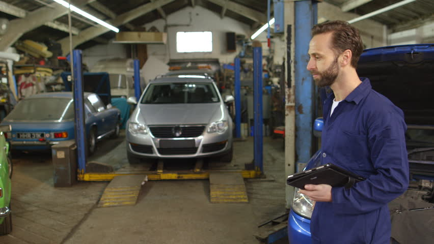 Mechanic explaining expenses for car repair to his customer