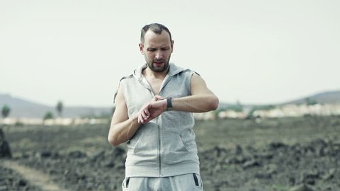 Man with smartwatch and woman jogging on desert, slow motion shot at 240fps